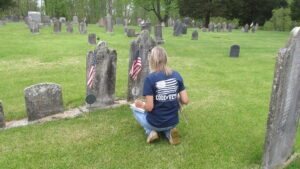 Author Jessica James placing flags on veterans graves for Memorial Day